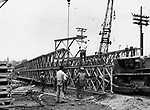 A second link in the chain of temporary bridges to span the Naugatuck River is nearing completion on the site of the former Washington Avenue bridge which was washed away in the flood. This is the second of three bridges promised the city. The first is operating at South Leonard Street and a third is promised for Platts Mills. 06 September 1955.