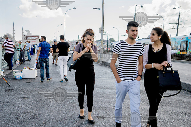 A woman lights up a cigarette while crossing the Galata Bridge.