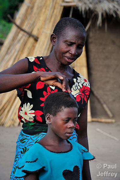 "Hilda Simon, 57, prepares her granddaughter Annie, 10, for school in Dickson, a village in southern Malawi. Annie and her sister and brother are orphans, and were taken in by their grandmother when their parents died four years ago. Many African villages like this have been hard hit by disease, including HIV and AIDS, leaving children to be cared for by relatives. Yet this village has also been hard hit by drought in recent years, leading to chronic food insecurity, especially during the ""hunger season,"" when farmers are waiting for the harvest. In addition to providing emergency food, the ACT Alliance is working with farmers in this village to switch to alternative, drought-resistant crops, as well as installing an irrigation system and utilizing other improved techniques to increase agricultural yields."