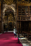PORTUGAL, Coimbra, a woman is visiting inside Biblioteca Joanina in Coimbra University