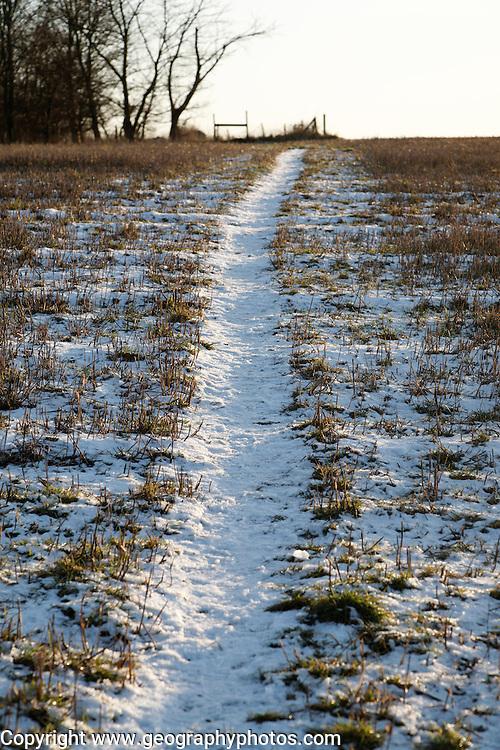 Snow covered path climbing hillside toward distant stile, Shottisham, Suffolk, England, UK