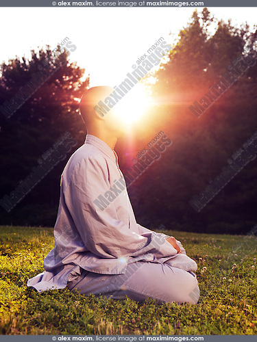 Shaolin monk meditating outdoors with sun rising behind him, artistic enlightenment concept