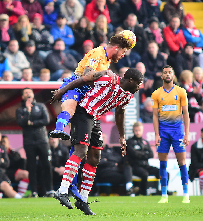 Lincoln City's John Akinde vies for possession with  Mansfield Town's Ryan Sweeney<br /> <br /> Photographer Andrew Vaughan/CameraSport<br /> <br /> The EFL Sky Bet League Two - Lincoln City v Mansfield Town - Saturday 24th November 2018 - Sincil Bank - Lincoln<br /> <br /> World Copyright © 2018 CameraSport. All rights reserved. 43 Linden Ave. Countesthorpe. Leicester. England. LE8 5PG - Tel: +44 (0) 116 277 4147 - admin@camerasport.com - www.camerasport.com