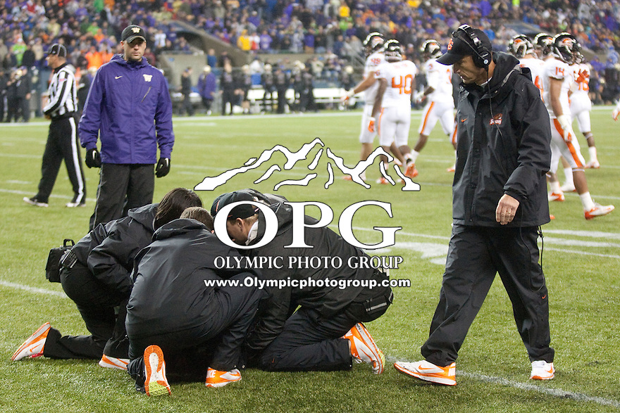 OCT 27, 2012: Oregon State trainer and head coach Mike Riley attend to Marcus Wheaton after he was knocked out of the game against Washington.  Washington won 20-17 over Oregon State at CenturyLink Field in Seattle, WA...
