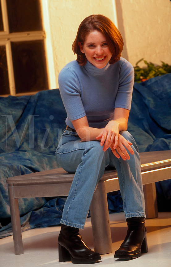 A smiling young woman sits casually in her livingroom.