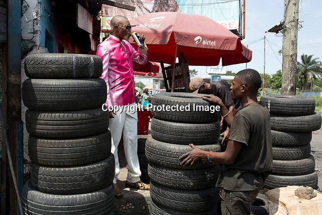 "KINSHASA, DEMOCRATIC REPUBLIC OF CONGO - FEBRUARY 11: Weston Mwene Kibambe, a Sapeur (and business man) dresses in his favorite suit at at his tire shop on February 11, 2017 in Kinshasa, DRC. The word Sapeur comes from SAPE, a French acronym for Société des Ambianceurs et Persons Élégants. or Society of Revellers and Elegant People. It also means to dress with ""elegance and style"". Most of the young Sapeurs are unemployed, poor and live in harsh conditions in Kinshasa, a city of about 10 million people. For many of them being a Sapeur means they can escape their daily struggles and dress like fashionable Europeans. Many hustle to build up their expensive collections. Most Sapeurs could never afford to visit Paris, and usually relatives send or bring clothes back to Kinshasa. Mr. Kibambe owns a small business, a tire repair shop, and he also sells used tires. (Photo by Per-Anders Pettersson)"