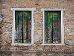 Two shuttered windows, along Fondamenta dei Vetrai on the main canal of Murano, Italy