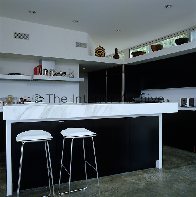 A pair of chrome and leather contemporary bar stools at the marble-topped kitchen island in this black and white kitchen