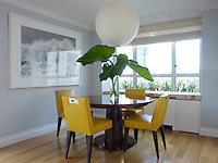 Bright yellow leather dining chairs are arranged around a pedestal table in the dining room