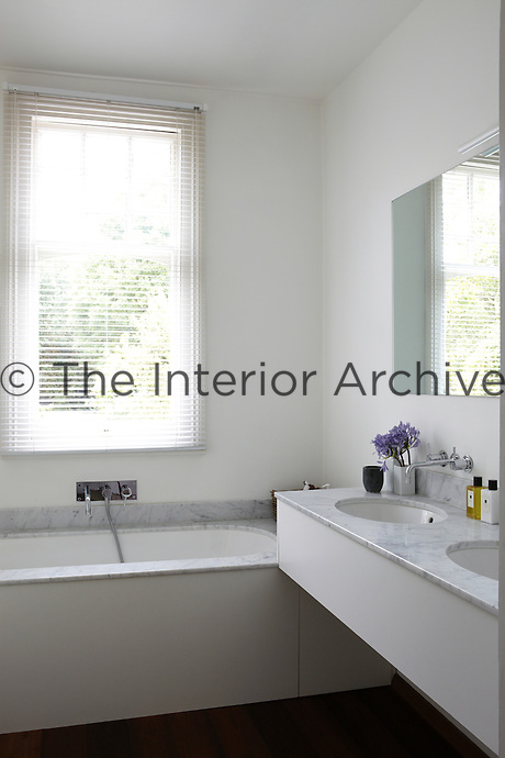 A modern white bathroom with a double sink and bath both with marble tops. The window is dressed with a venetian blind.