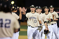 Keegan Maronpot (13) of the Wake Forest Demon Deacons high fives his teammates after their win over the UNCG Spartans at David F. Couch Ballpark on February 21, 2017 in  Winston-Salem, North Carolina.  The Demon Deacons defeated the Spartans 15-8.  (Brian Westerholt/Four Seam Images)