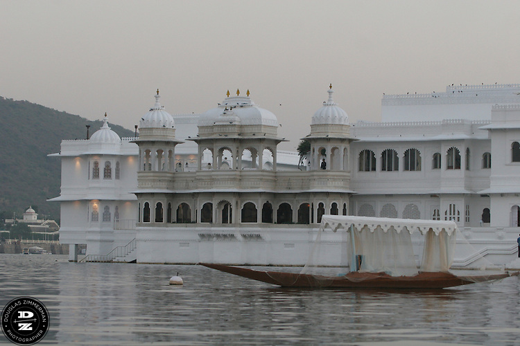 "View of the Lake Palace Hotel, which sits on Jagniwas Island in the center of Pichola Lake, in Udaipur, Rajasthan, India.  Udaipur is located in a valley surrounded by the Aravalli hills, and at its center is the Pichola Lake.  The scenic city has been described as ""the most romantic spot on the continent of India"" (by Colonel James Tod).  Photograph by Douglas ZImmerman"