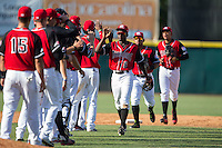 Eric Jenkins (5) of the Hickory Crawdads high fives his teammates following their win over the Delmarva Shorebirds at L.P. Frans Stadium on June 18, 2016 in Hickory, North Carolina.  The Crawdads defeated the Shorebirds 1-0 in game one of a double-header.  (Brian Westerholt/Four Seam Images)