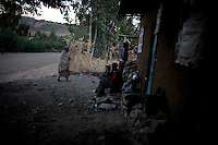 """An elderly woman walks to a corner shop while young intoxicated boys smoke outside a local bar in Walleke, once an Ethiopian Jewish town in the outskirts of the city of  Gonder, northern Ethiopia on Saturday January 10 2009..Ethiopian Jews, who in the past were not allowed to own land, most of which was in the hands of the Orthodox church become able craftsmen producing pottery and threading cotton. All of them were airlifted to Israel through the years and none of them remains today in Walleke. Today the town is a tourist destination for whom are interested in The Beta Israelis and their history...Gonder hosts a population of around 9000 so called """"Falash Mura"""", supposed Ethiopian Jews who were forced to convert to Christianity. The Israeli Government is still verifying their claims  and if a clear link between them and Israel would be established they would have the right to return to their mother land. In the mean time Israeli and other Jewish non governmental organizations are working in support of this community."""