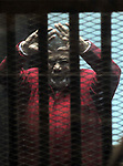 FILE PHOTO: Ousted Egyptian president Mohammed Morsi gestures as he sits behind bars during his trail as part of the so-called 'Qatar espionage' case, in a court in Cairo on january 2, 2015. Former President Mohamed Morsi died on Monday in court after the conclusion of a trial session in the espionage lawsuit, Egyptian state TV said. Photo by Amr Sayed