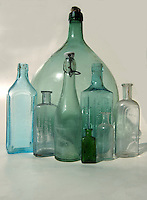 Collection of diiferent shaped and assorted old bottles.