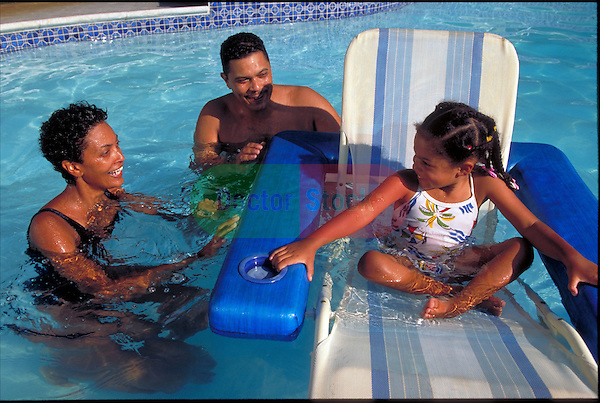 smiling family playing in swimming pool