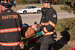 A mass casualty incident victim on a backboard being carried by EMTs and firefighters