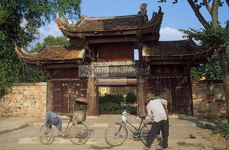 Asie/Vietnam/Hanoi: Cycliste devant la Pagode de Kim Lien