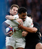 Photo: Richard Lane/Richard Lane Photography. England v New Zealand. QBE Autumn International. 08/11/2014. Ebgland's Billy Vunipola is tackled by New Zealand's Richie McCaw and Charlie Faumuina.