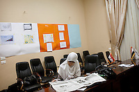 Dr Heba, one of the Muslim Sisters, waits for other Sisters whilst read a newspaper in the Muslim Brothers' Media Center in Mansour Street, Cairo. Egypt, June 2012.