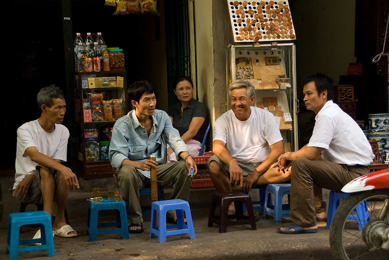 Men sit and have a cup of tea in Hanoi, Vietnam. It's very common for people to sit on these small stools and have a cup of tea or meal at the side of the road.