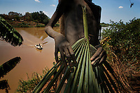 On our first trip in early 2009 I photographed this Mursi kid holding a leaf frond on the banks of the Omo River.  The frond is used as a chair... something to sit on.  And the boat in the background is the only boat we saw on the river during an extensive six week transect from the highlands where the river starts all the way down to Kenya where the river dumps into Lake Turkana.