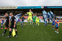 The players enter the field during the Sky Bet League 2 match between Wycombe Wanderers and Colchester United at Adams Park, High Wycombe, England on 27 August 2016. Photo by Liam McAvoy.