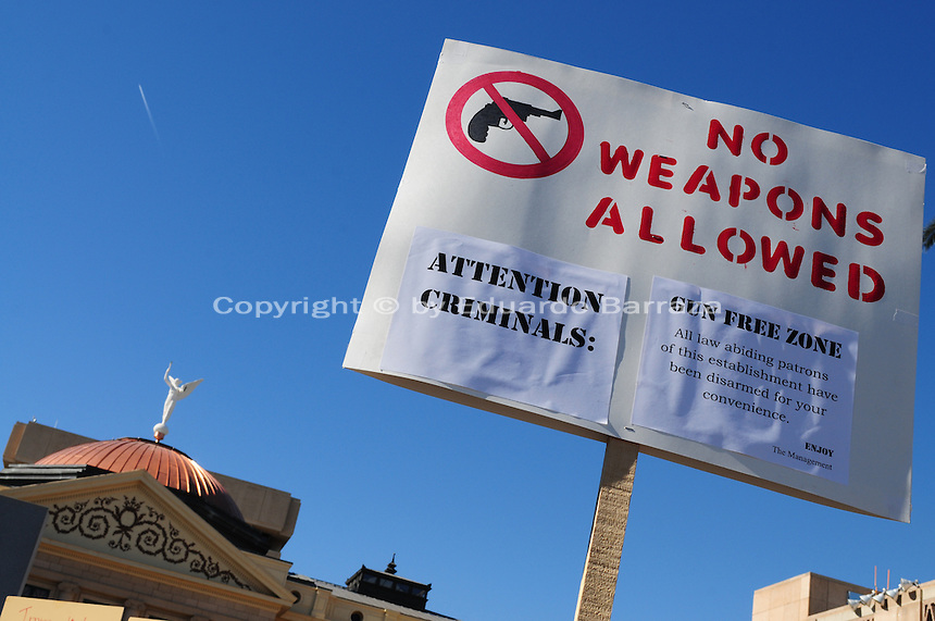 "Phoenix, Arizona. January 19, 2013 - A protest sign lifted over the crowd during Saturday's rally in Phoenix protest a gun control that would ""give criminals a gun free zone."" As President Barack Obama proposed new gun regulations last week, gun owners demonstrated against it with national ""Guns Across America"" rallies to defend the Second Amendment. Dozens showed up at the Arizona State Capitol, many of them carrying weapons. Photo by Eduardo Barraza © 2013"