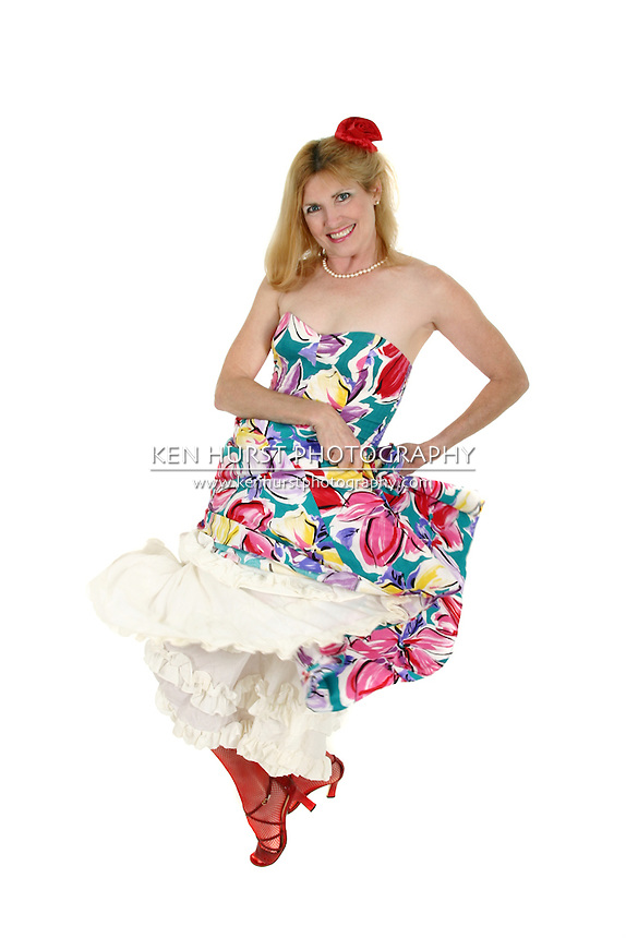 Beautiful middle aged woman performing the Can Can wearing mesh stockings on her legs and a flower in her hair.