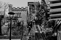 """Switzerland. Canton Ticino. Lugano. Tourists walk up and down the stairs close to """"Funicular degli Angioli. The Funicular degli Angioli (Italian: Funicolare degli Angioli) was a funicular railway and inclined lift in the city of Lugano. It linked a lower terminus near the lakeside and the church of Santa Maria degli Angioli with an upper terminus adjacent to the Hotel Bristol. The upper station was on the third floor of a tower, linked with a footbridge to the hotel. The line had a single track and single car, which was balanced by a vertically operating counterweight in the tower. When in operation, the line was 142 metres in length and climbed a vertical distance of 53 metres with a maximum gradient of 44% and an average gradient of 38.7%. The line opened in 1913. In 1973 it was gifted by its owner to the City of Lugano. The Hotel Bristol closed in 1981, and the funicular followed in 1986. The line remains in existence, but in an abandoned state. In 2012 the line was listed as a cultural property of regional significance. It is estimated that restoration  would cost CHF2.6 million. 30.12.2018 © 2018 Didier Ruef"""