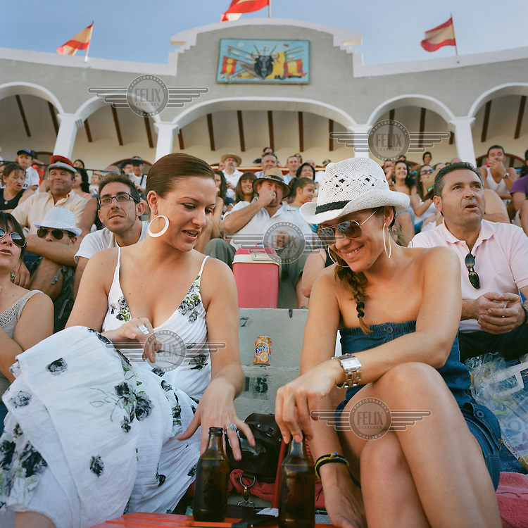 Two women sit with beers in the stalls of the town's bullring during an afternoon's bullfighting.