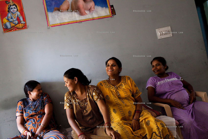"Women sit around in the Akanksha surrogate house as posters of babies and religious symbols adorn the walls...Shilpa Ben Praveenbhai Maikwan, 28, (2nd from left) is carrying a baby for her clients from Delhi, India. ""we do this so our children will not lead a life such as ours, we want a better life for them."".(left to right) .Unknown; Shilpa Maikwan; Indu Ben Dasrathbhai Pawar (Also photographed in ultrasound room; ""there is a fear about health... then we think that its in gods hands and pray that its a smooth pregnancy); Martha Sanjay Chauhan (35, christian);..The Akanksha Infertility Clinic in Anand, Gujarat, India, is known internationally for its surrogacy program and currently has over a hundred surrogate mothers pregnant in their environmentally controlled surrogate houses."