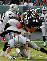 Oakland Raiders defensive back Renaldo Hill (22) and Stuart Schweigert (30) knock the ball loose from Philadelphia Eagles tight end L.J.Smith (82) and caused a fumble with Oakland recovering in the fourth quarter in Philadelphia, September 25, 2005. REUTERS/Bradley C Bower