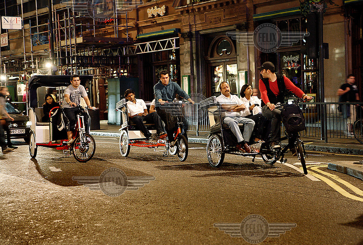 Tricycle taxis transport people through the West End, central London late on a summer night.