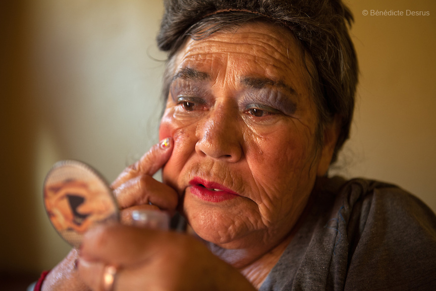 Amalia, a resident of Casa Xochiquetzal, puts on makeup before going out to work on the streets of the La Merced neighborhood of Mexico City, Mexico on October 15, 2010. Amalia, 66, is from Michoacán and came to Casa Xochiquetzal when it first opened its doors. She wears a wig and pads her bra. She is very animated; words and songs come easily to her. She has also suffered from schizophrenia for 22 years, but despite hearing voices, she works hard not to lose touch with reality. As a way of earning a little money, she gathers plastic bottles to recycle and also helps to sell clothes in a stand operated by her boyfriend of 31 years. Casa Xochiquetzal is a shelter for elderly sex workers in Mexico City. It gives the women refuge, food, health services, a space to learn about their human rights and courses to help them rediscover their self-confidence and deal with traumatic aspects of their lives. Casa Xochiquetzal provides a space to age with dignity for a group of vulnerable women who are often invisible to society at large. It is the only such shelter existing in Latin America. Photo by Bénédicte Desrus