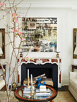 In the living room, above the fireplace a painting by Canan Tolon is flanked by 19th century Italian mirrors. The 1940s glass-topped cocktail table in front is attributed to Jacques Quinet.
