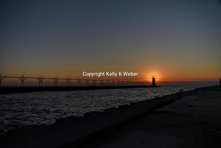 The South Haven lighthouse glows as the sunsets behind it on a beautiful warm November eve.