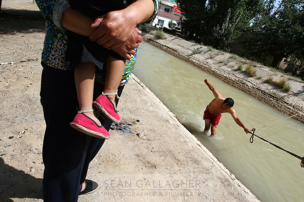 A man swims in a water irrigation channel trying to catch small fish. Desertification is the process by which fertile land becomes desert, typically as a result of drought, deforestation, or inappropriate agriculture. Dunhuang, Gansu Province. China