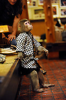 Fuku-chan, 6, a Japanese monkey waiter, takes a rest in an Izakaya bar in north of Tokyo, Japan. The six year old monkey looks after the guests hot towels by taking them from the steamer oven and delivering them to all guests. The bar is extremely popular amongst people from all over Japan who come to see the monkey waiters.