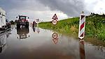 BLEISWIJK - Aan de voet van een in aanbouw zijnd viaduct over de snelweg A12 bij Bleiswijk is het wegdek door gebrekkige riolering overstroomd met water. Hoewel de verkeersborden een maximum snelheid van 50 km/uur lijken toe te staan vanwege de werkzaamheden maakt de wateroverlast het doorrijden volkomen onmogelijk en wordt het water weggezogen en afgevoerd door een traktor met watertank. COPYRIGHT TON BORSBOOM