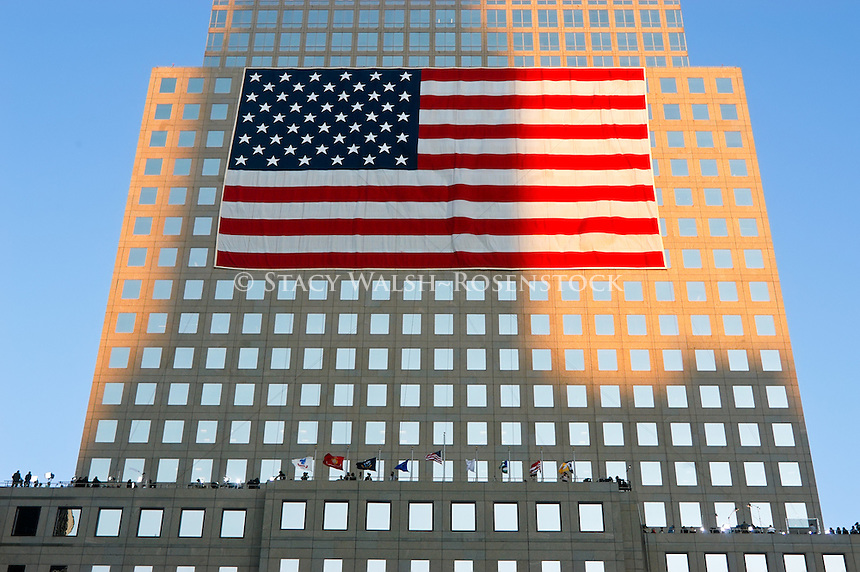11 September 2003  New York, NY -- Massive American Flag hangs from the facade of  the World Trade Center, as the sun begins to rise over Ground Zero. On the balcony below media gets in place to cover the memorial service marking the second anniversary of the World Trade Center attack.