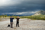 Two men take photographs with the Norwegian mountains behind them.