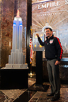 Former men's national team player Tab Ramos poses for a photo next to a model of the Empire State Building lit in the Red White and Blue colors of the US Soccer Federation during the centennial celebration of U. S. Soccer in New York, NY, on April 05, 2013.