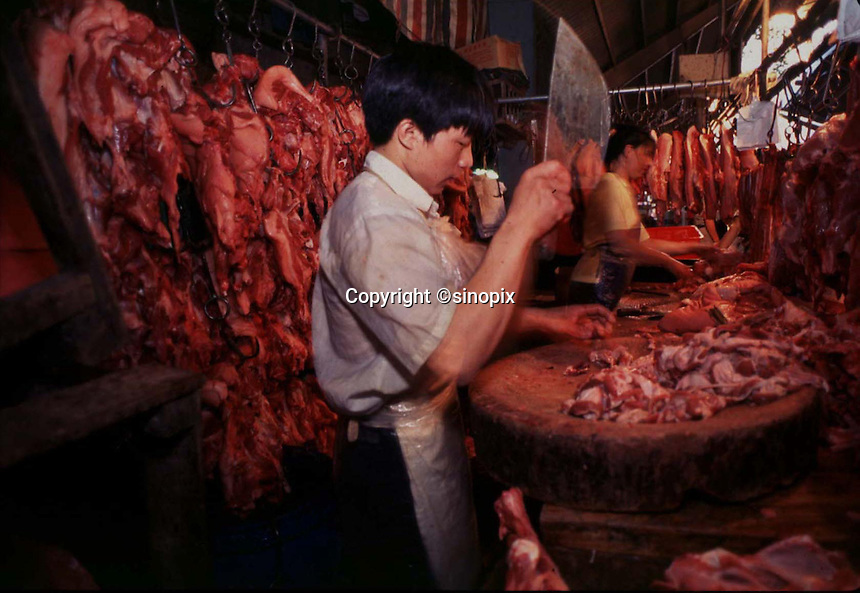 Workers at Qing Ping meat market in Guangzhou prepare freshly-killed pork for the market that day.