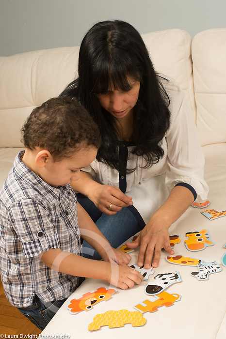 Two year old toddler boy doing cardboard jigsaw puzzle with mother's help