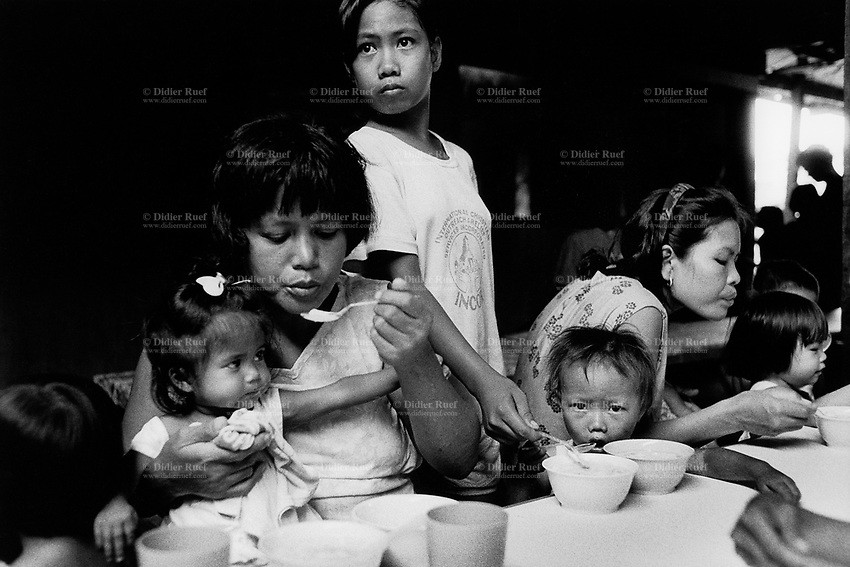 "Philippines. Luzon Region. Manila. Tondo area. Smokey mountain is a rubbish dump. Life on a garbage heap. Feeding center for malnourished children at the catholic church "" Grace children save"". Families, mothers and kids, sisters and brothers. Food. © 1992 Didier Ruef ."