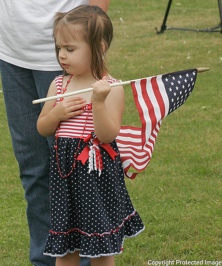 Mayla Monaghan age 2 holds a flag during one of the Stoughton Memorial Day ceremonies at of the Holy Sepulcher Cemetery in Stoughton on Monday..(Photo by Gary Wilcox).