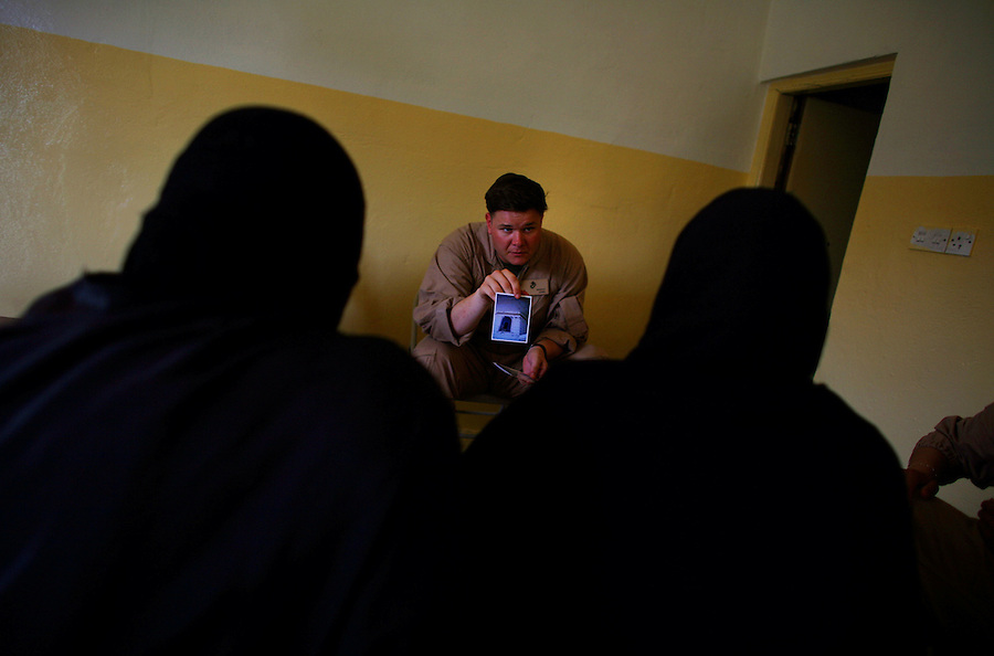 At an outreach center, a Marine sergeant tasked to screen applicants looking for compensation for damages, deaths, or injuries caused by US forces during four years of fighting in Ramadi holds a photo presented to him by two women on Wednesday May 23, 2007 as proof of damage to the walls of their home caused by automatic weapons. The claim was denied because of a strong suspicion on the part of the sergeant that the home had been used by insurgents as a fighting position and because the women's story changed with each question they were asked.