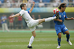 07 August 2008: Brian McBride (USA) (left) kicks the ball away from Takuya Honda (JPN) (16).  The men's Olympic team of the United States defeated the men's Olympic soccer team of Japan 1-0 at Tianjin Olympic Center Stadium in Tianjin, China in a Group B round-robin match in the Men's Olympic Football competition.